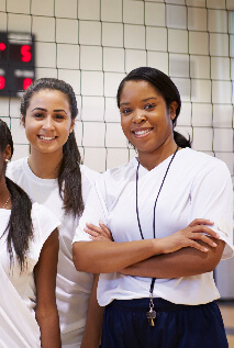 Volleyball coach standing beside her players